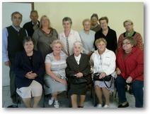 Denise assise au centre avec l'équipe de la paroisse lors d'une relecture funérailles