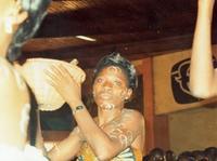 Geste d'offrande au cours d'une messe. Les ronds blancs du maquillage sur le visage sont réalisés avec du kaolin, matériau noble utilisé lors des fêtes